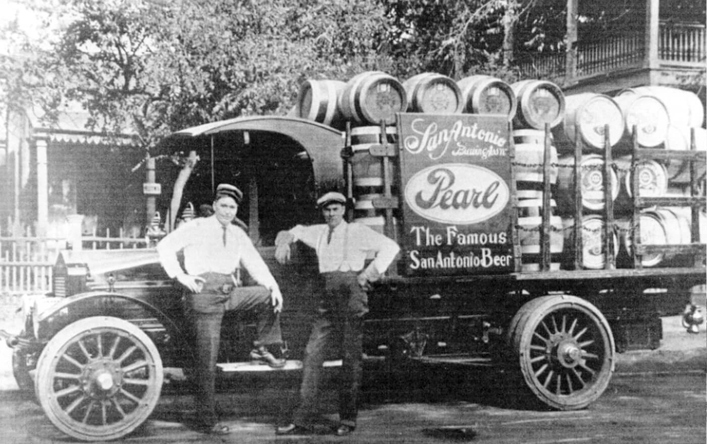 A black and white picture of two men in front of the famous San Antonio's Pearl beer truck.