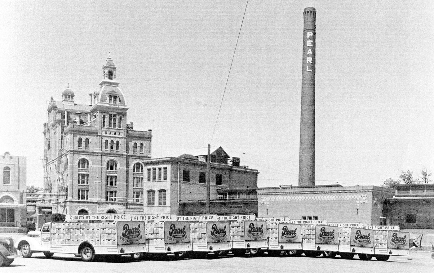 A black and white picture of a mid-century truck fleet in front of the Pearl Brewery.
