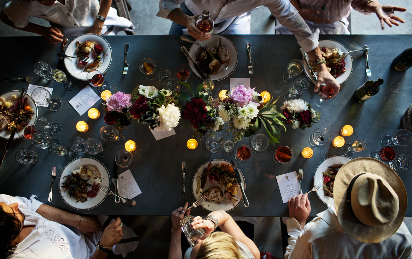 A picture of a grey table decorated with four flower bouquets and six friends eating around the table.