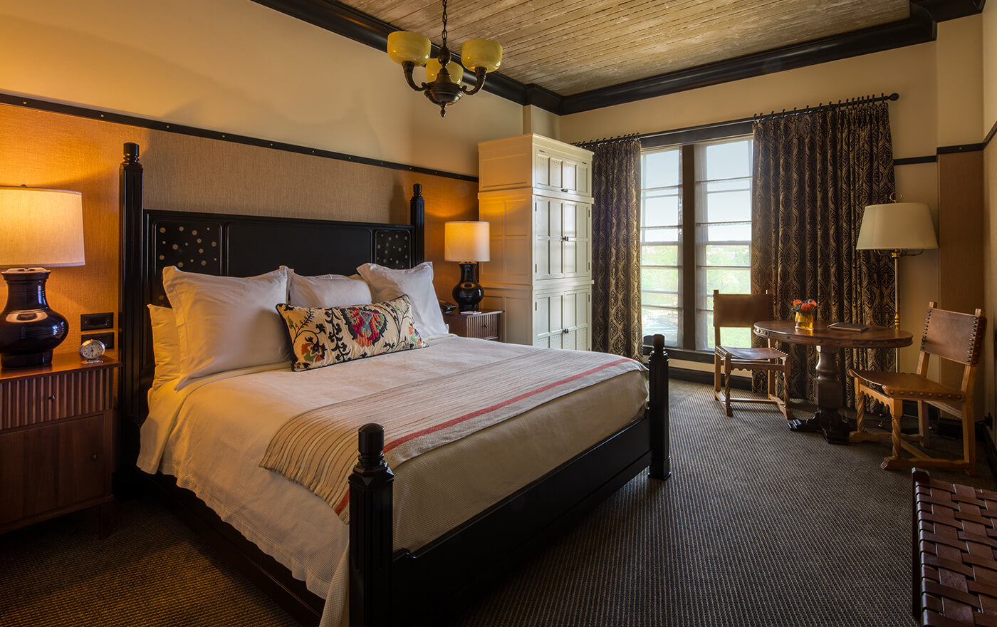 A picture of the bedroom of Hotel Emma's Classic room options. Pictured is a king size bed with two nightstands and two windows.