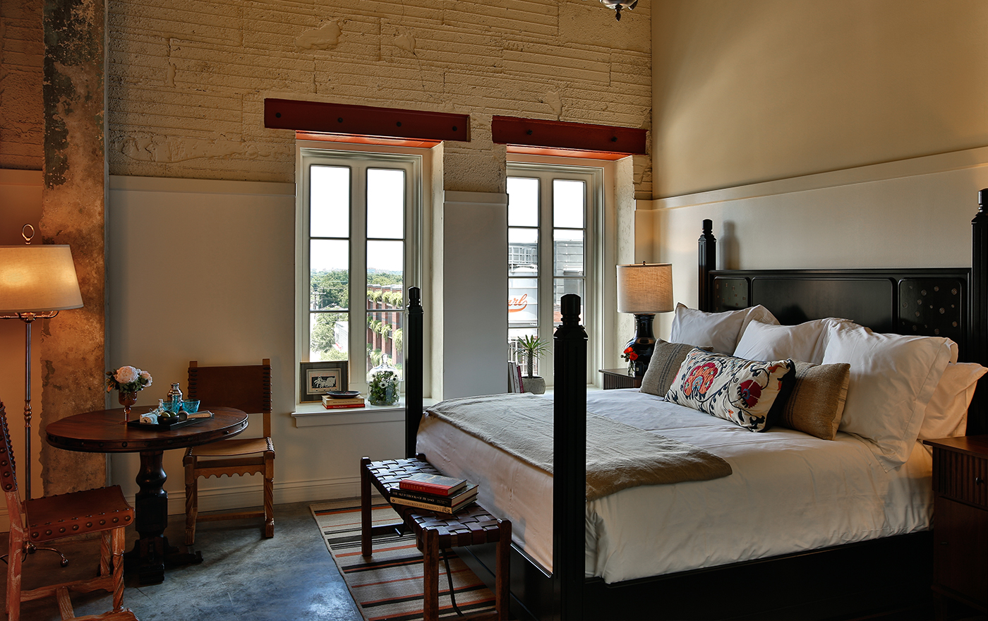 A picture of the bedroom at Hotel Emma's Landmark rooms. Pictured is a king sized bed with a table and two chairs next to a window.