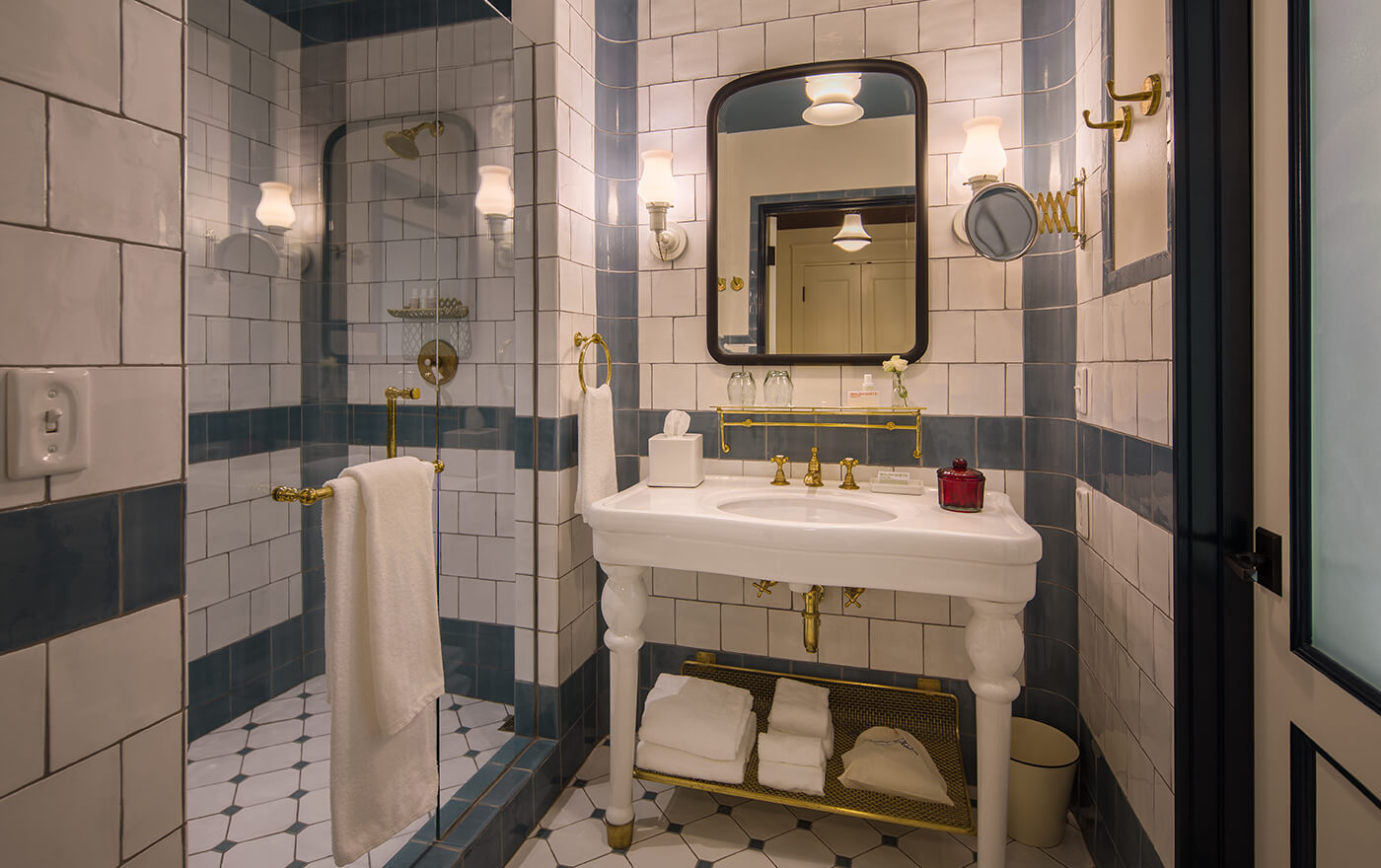 A picture of the bathroom at Hotel Emma's Landmark rooms. Pictured is white and gold vanity next to the shower.