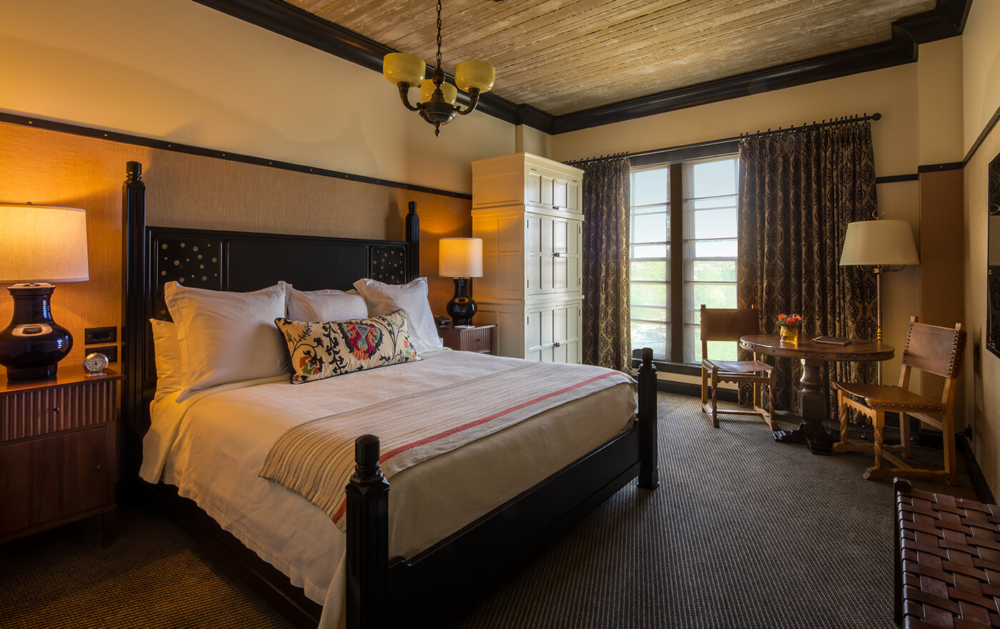 A picture of the bedroom in Hotel Emma's artesian rooms. Pictured is a king sized bed with nightstands and a table with two chairs.
