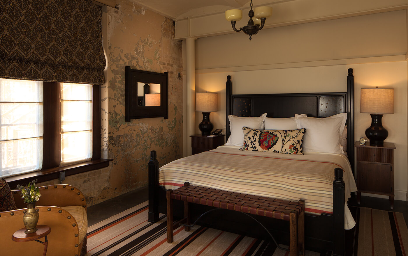 A picture of the bedroom in Hotel Emma's plaza suite option. Pictured is a king sized bed with nightstands and a window.