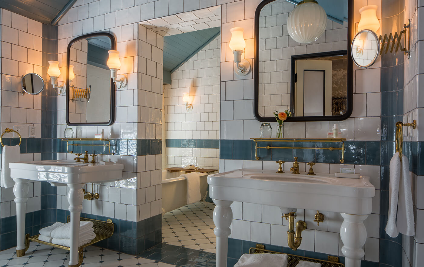 A picture of the bathroom of Hotel Emma's Martizen suite option. Pictured is a double vanity with a claw white foot tub.
