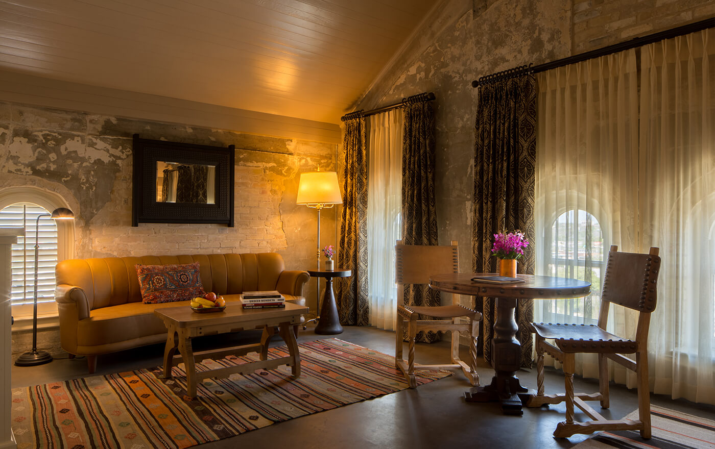 A picture of the bedroom of Hotel Emma's Martizen suite option. Pictured is a table with two chairs, and a couch and coffee table.