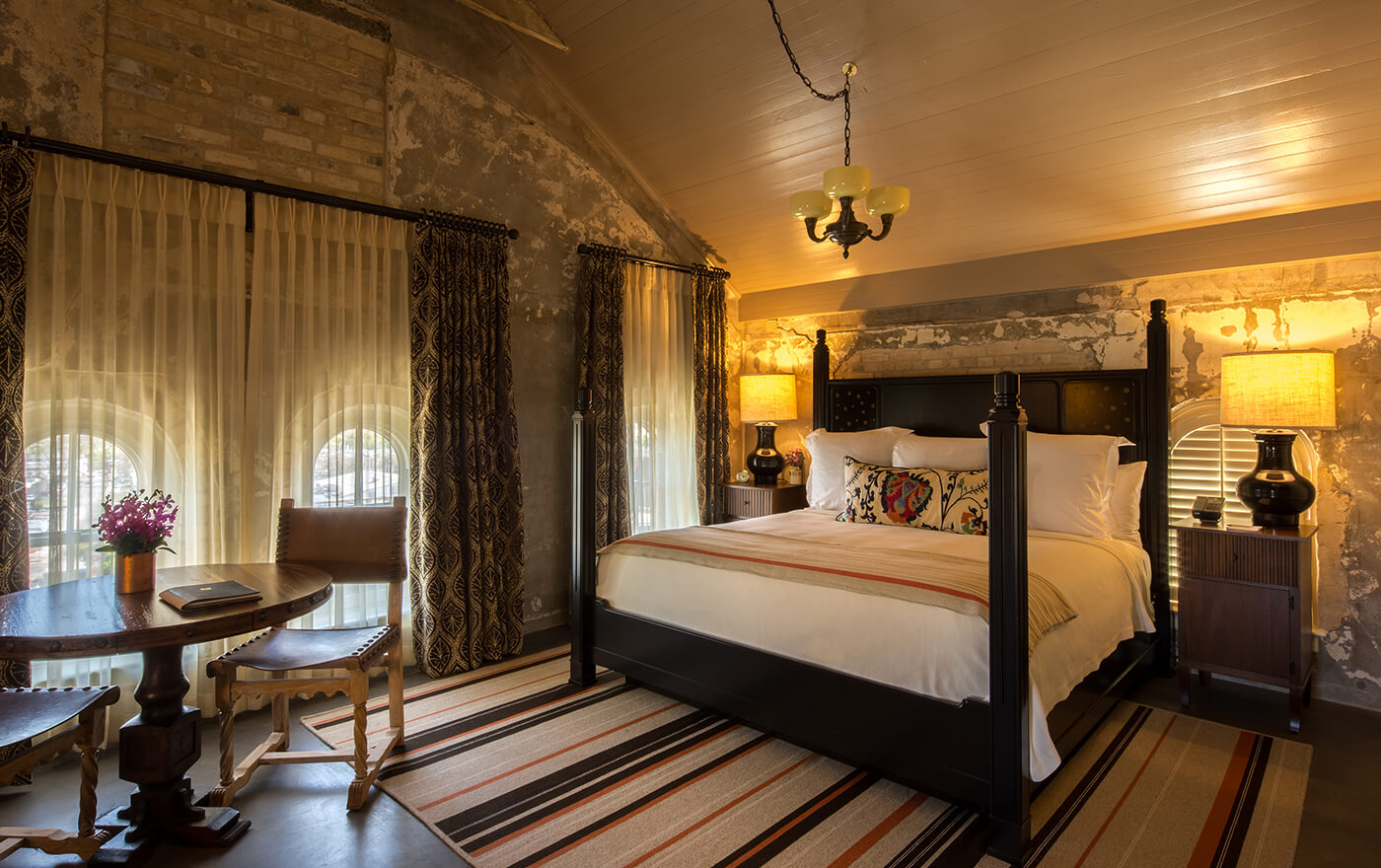 A picture of the bedroom of Hotel Emma's Martizen suite option. Pictured is a king sized bed with nightstands and a table with two chairs.