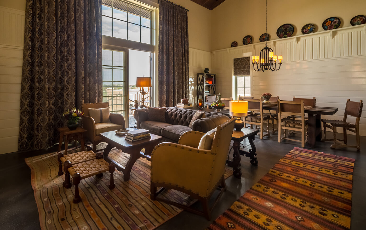 A picture of Hotel Emma's Otto suite option. Pictured is the spacious living room with tall windows, a seating arrangement and an 8 person table.