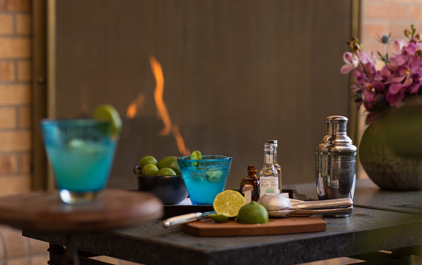A picture of cocktails pictured on a table with limes.