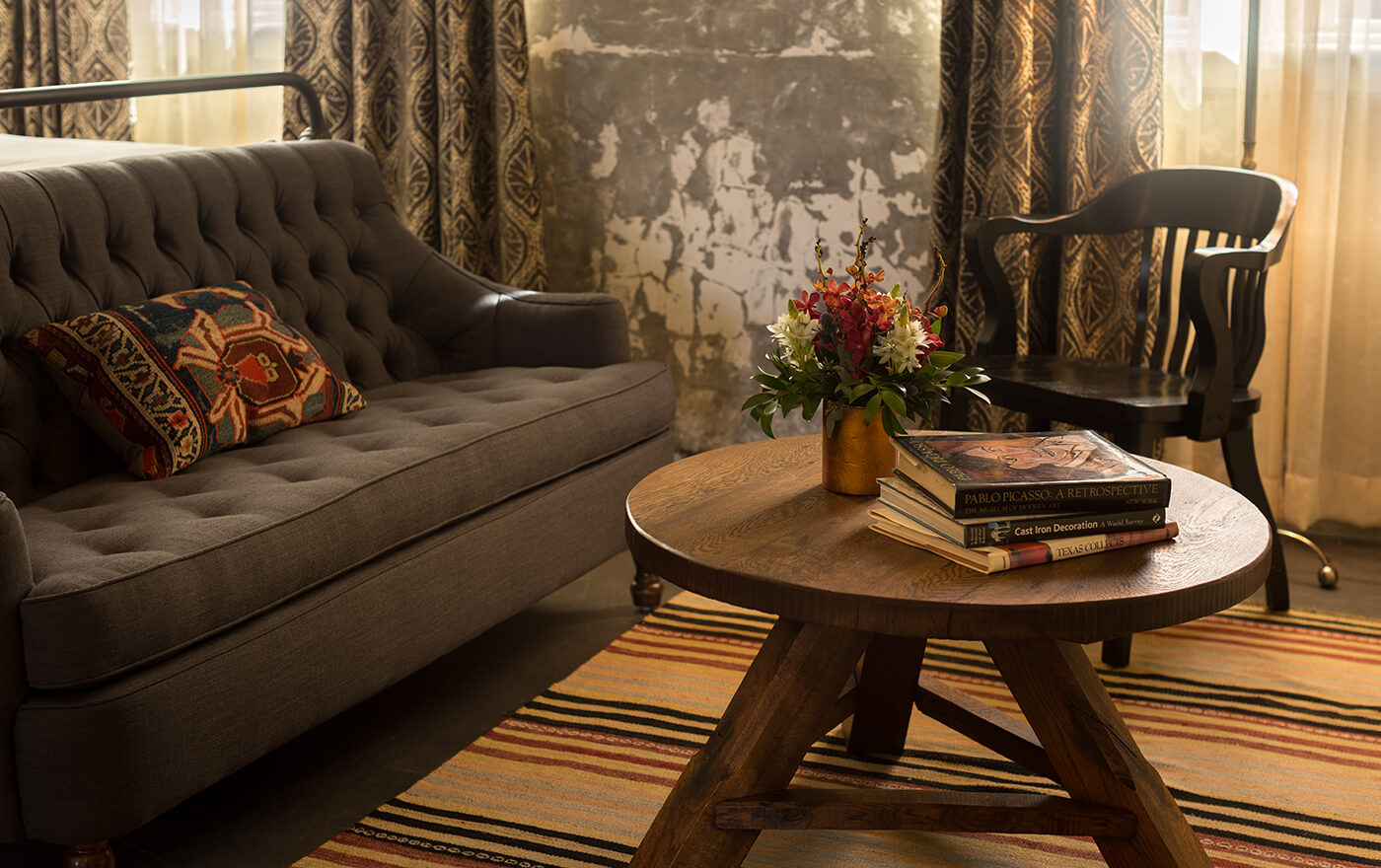 Picture of a grey couch with a wooden table with a bouquet of flowers and some books in Hotel Emma's Emma Koehler suite option.