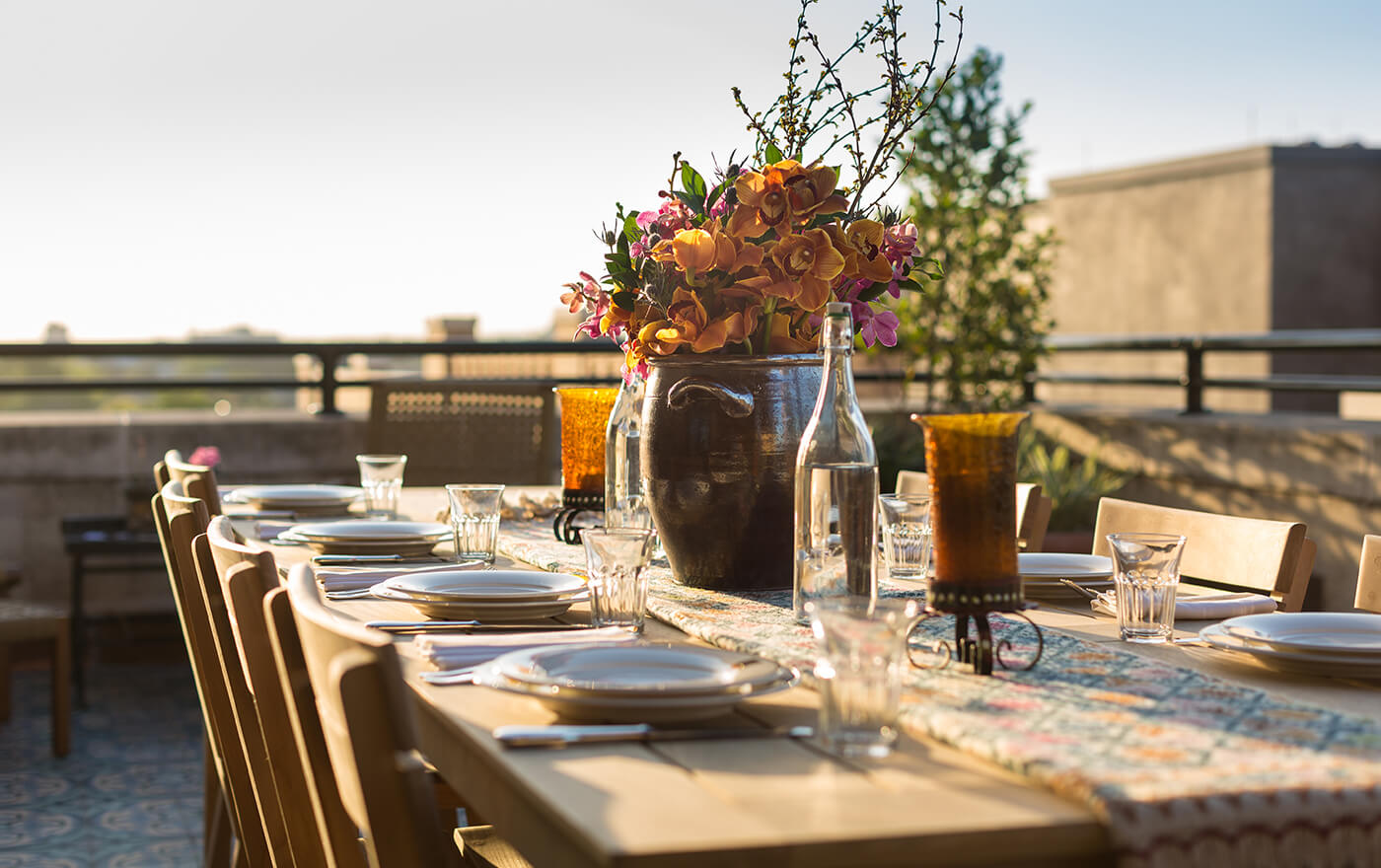 A picture of the terrace of Hotel Emma's Emma Koehler suite option. Pictured is an 8 person table topped with a bouquet of orange and pink flowers with a view of the city.