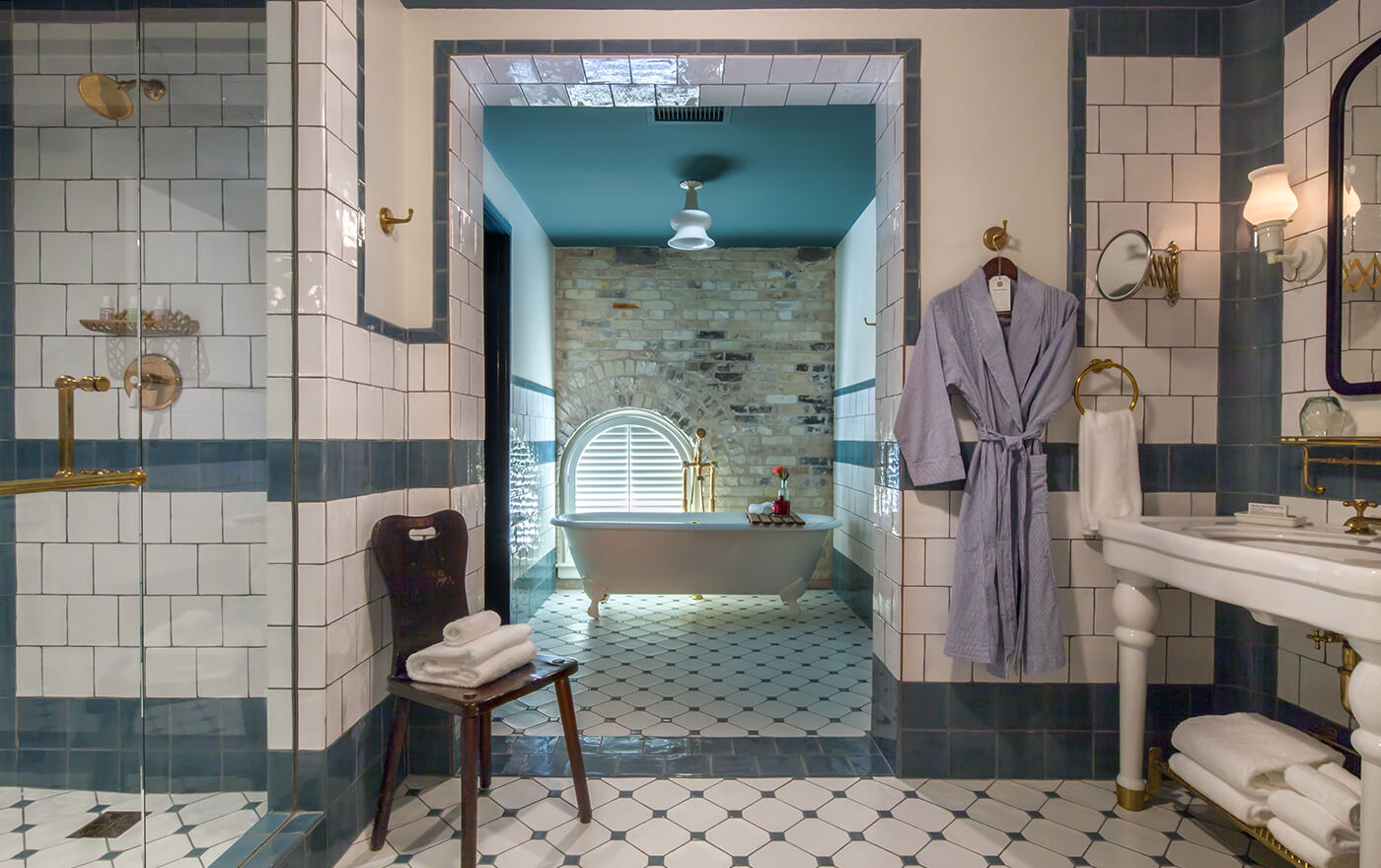 Picture of the luxurious bathroom in Hotel Emma's Garret room option. The picture includes the shower, a white claw foot tub, a white and gold sink with a light blue Hotel Emma robe.