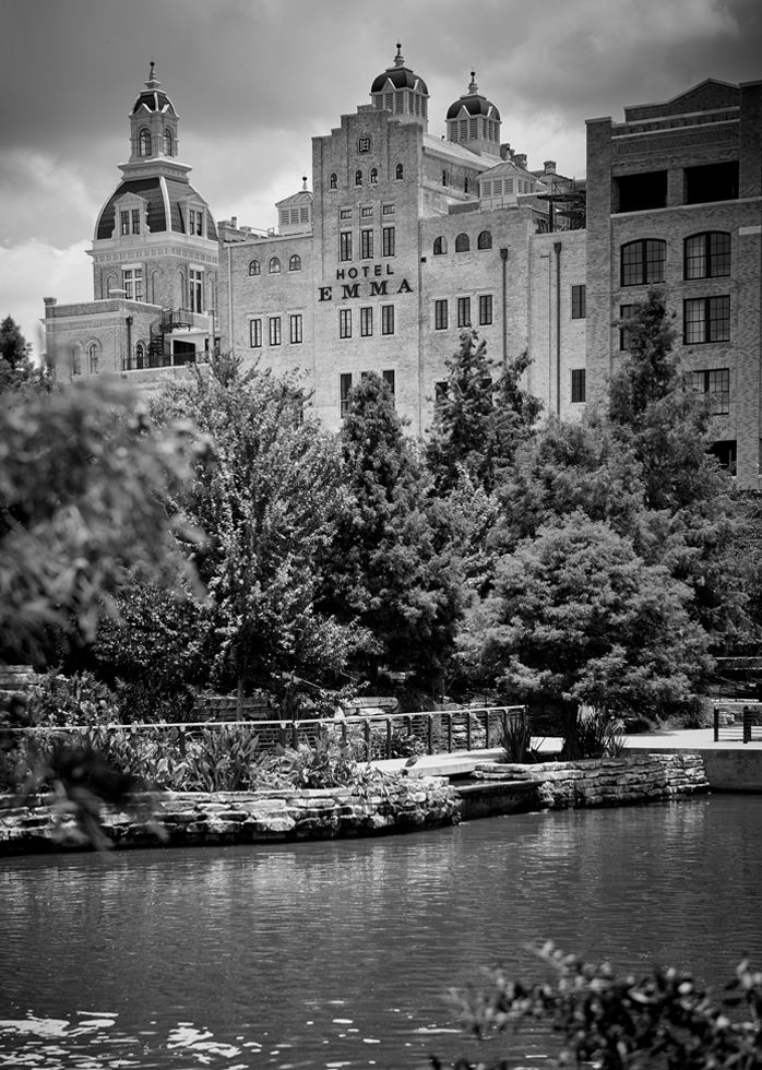 A black and white picture of a view of Hotel Emma from the Riverwalk.