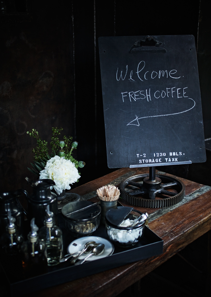 A picture of a welcome sign that reads fresh coffee next to the coffee station.