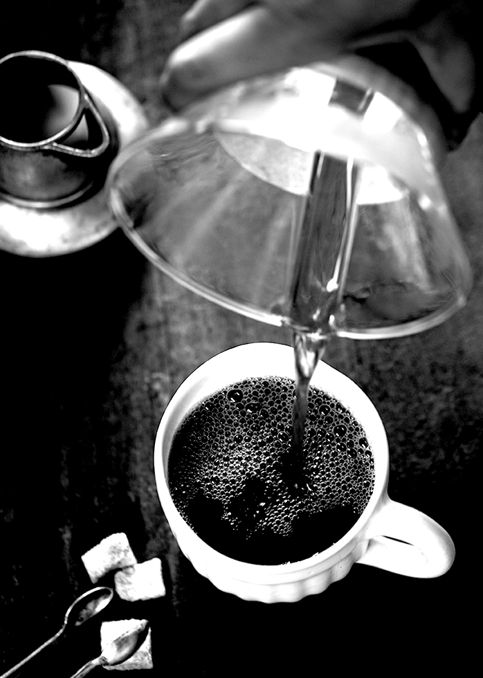 A black and white picture of coffee being poured.