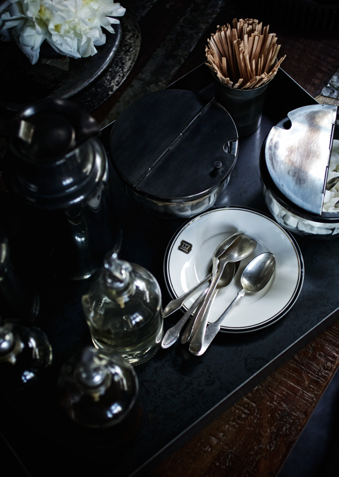 A picture of silver spoons next to sugar and stirring sticks for coffee.