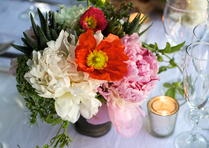 A picture of an exquisite bouquet with white, orange and pink flowers.