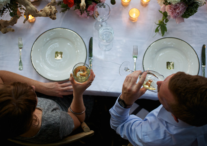 An aerial view of two people dining with white wine.