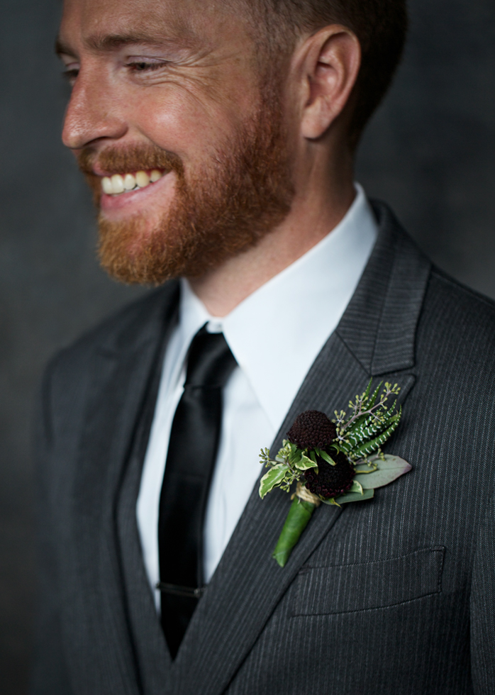A man wearing a suit with a his wedding Boutonnière smiling.