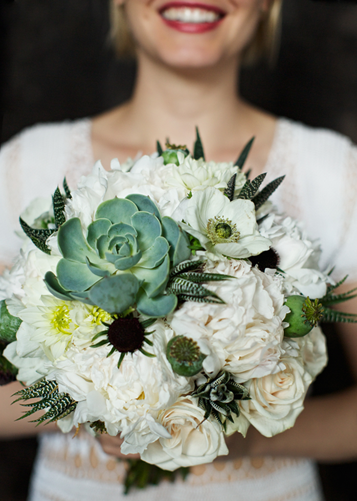 A picture of a women in a wedding gown with her bouquet of white and green flowers.