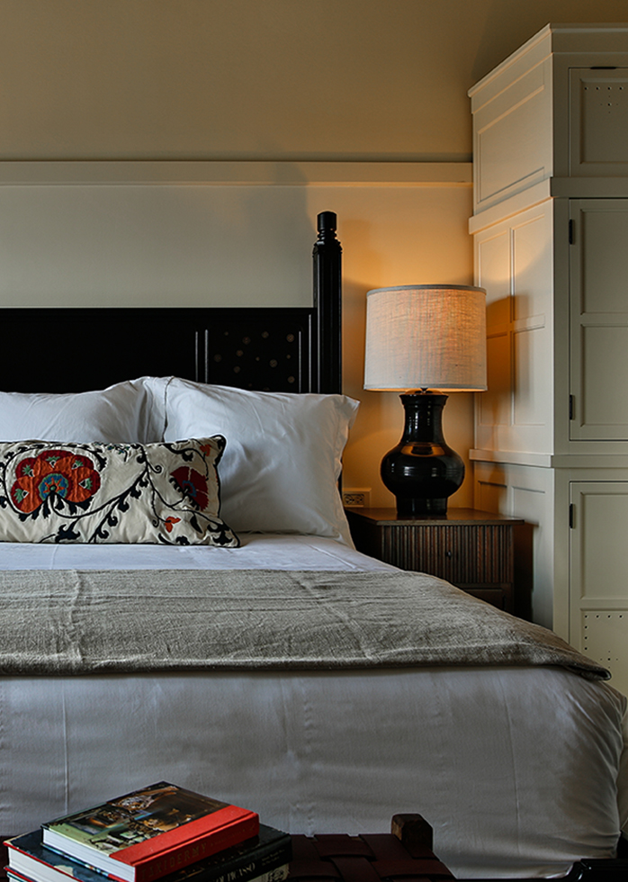 A picture of the bedroom of Hotel Emma's Classic room options. Pictured is a zoomed view of a white king size bed with a nightstand and a lamp.