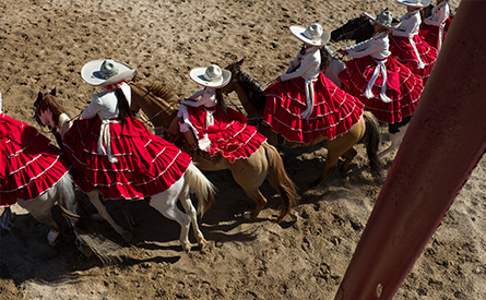 Six women in traditional Mexican clothing on horses