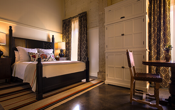 A picture of the bedroom of Hotel Emma's Classic room options. Pictured is a king size bed with nightstands and two windows.
