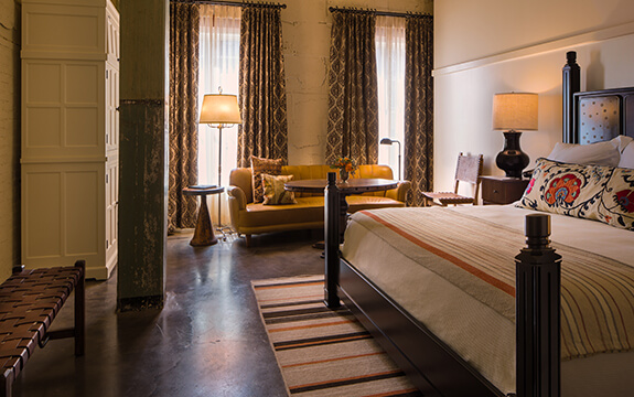 A picture of the bedroom at Hotel Emma's Landmark rooms. Pictured is a king sized bed with a couch next to the windows.