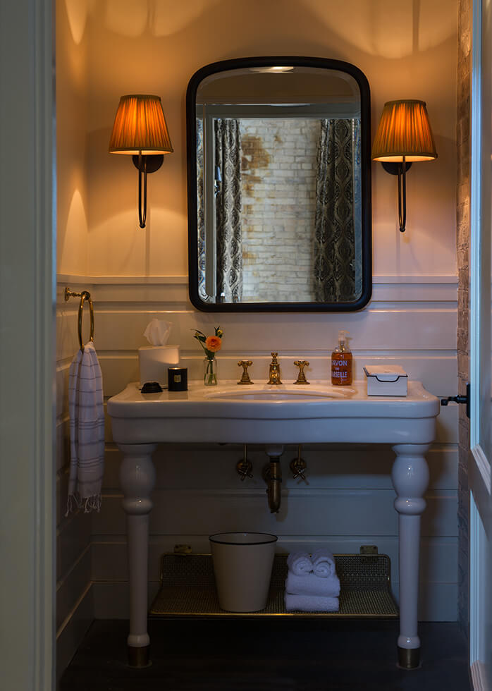 A picture of Hotel Emma's Maritzen suite's bathroom. Pictured is a white sink with a brown mirror above.