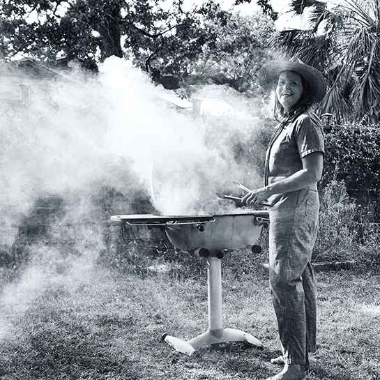 Paula Disbrowe smoking meat on a grill outside