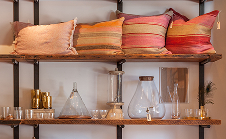 Pillows and various glass bottles on two shelves