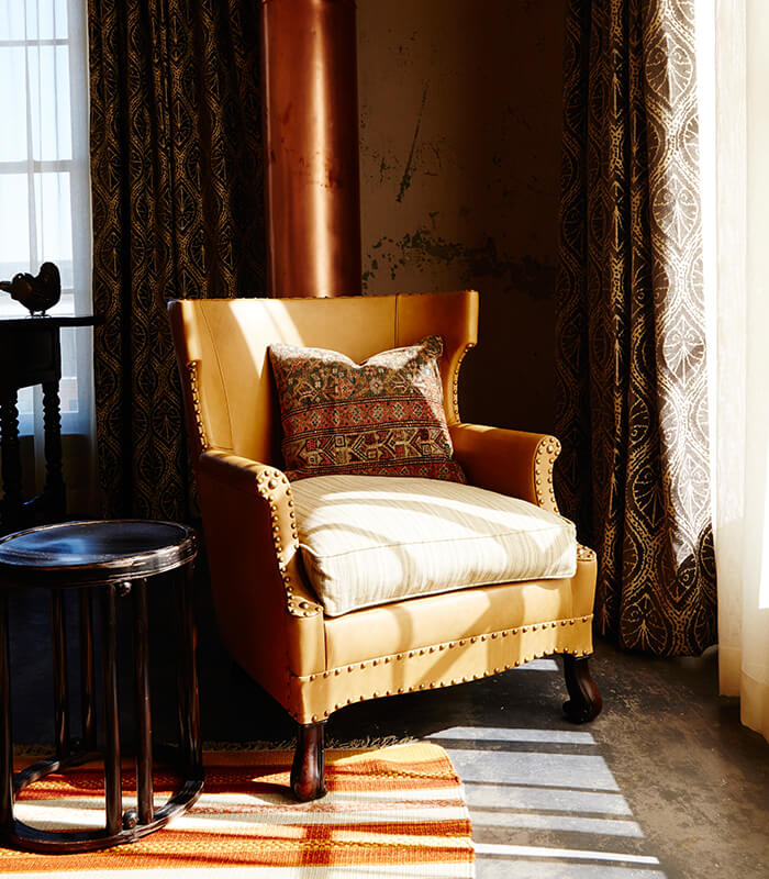 A picture of the bedroom in Hotel Emma's plaza suite option. Pictured is a chair with a decorative pillow facing a window.