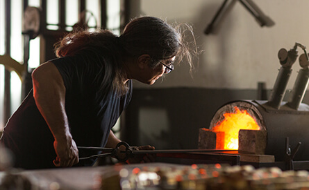 Blacksmith putting rod into furnace