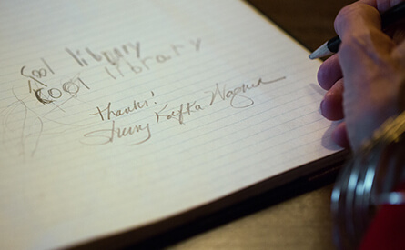 Woman signing her name in guestbook