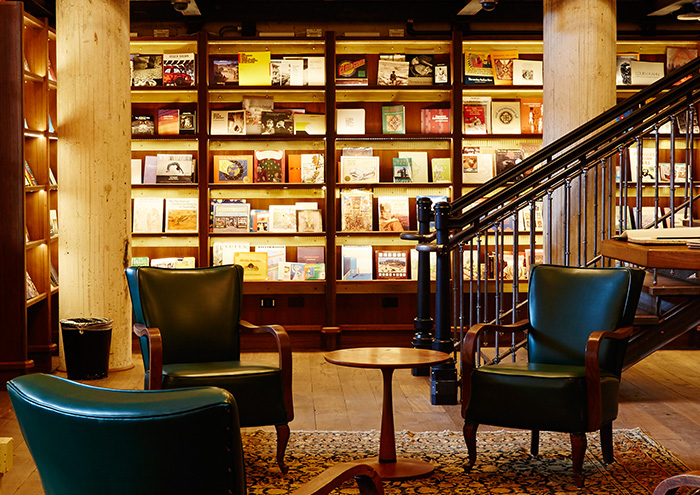 three leather chairs at the base of a staircase, surrounded by books in the hotel emma library